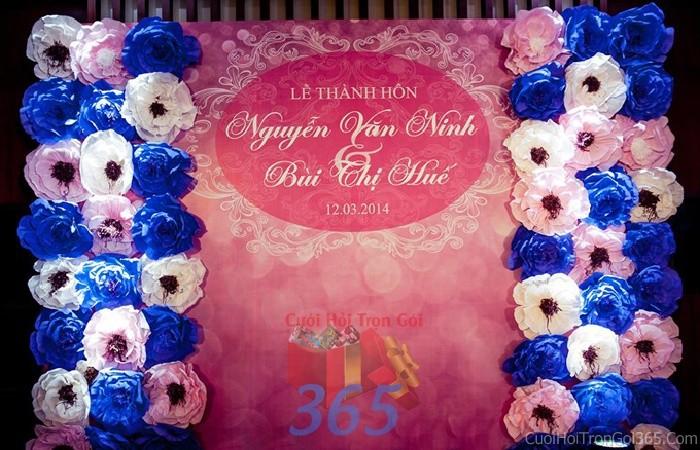 Backdrop hoa đám cưới tông màu hồng xanh dương từ hoa giấy kết dầy 2 bên và bảng tên chính BDNH41 : Mẫu cưới hỏi trọn gói 365 của công ty dịch vụ trang trí nhà tiệc cưới hỏi đẹp rẻ uy tín ở tại quận Tân Phú Sài Gòn TPHCM Gò Vấp