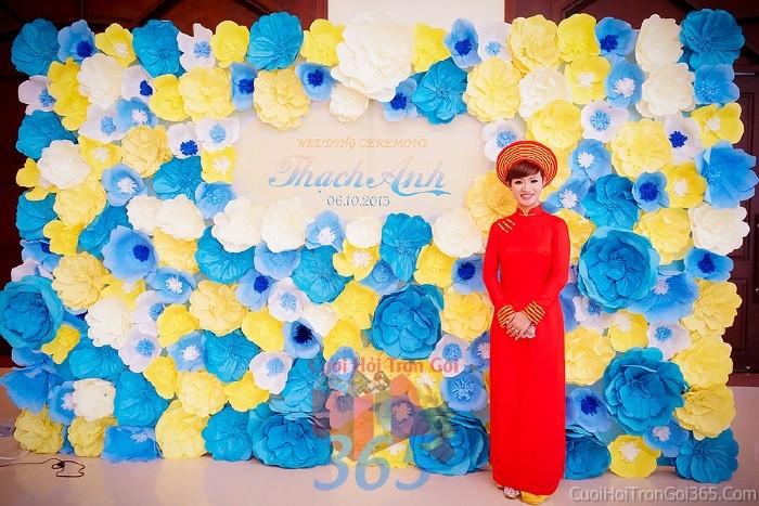 Backdrop hoa đám cưới tông màu vàng xanh biển tươi sáng, nổi bật với những bông hoa giấy lớn nhỏ chen BDNH53 : Mẫu cưới hỏi trọn gói 365 của công ty dịch vụ trang trí nhà tiệc cưới hỏi đẹp rẻ uy tín ở tại quận Tân Phú Sài Gòn TPHCM Gò Vấp
