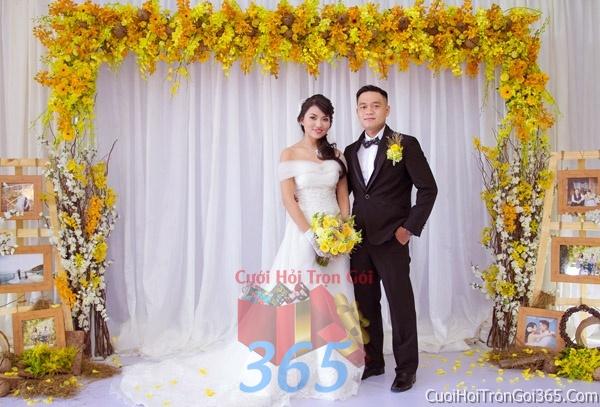 Phông cưới backdrop chụp hình đám cưới ngày lễ ăn hỏi làm bằng hạt giấy và hoa tươi tông màu vàng tươi BDNH35 : Mẫu cưới hỏi trọn gói 365 của công ty dịch vụ trang trí nhà tiệc cưới hỏi đẹp rẻ uy tín ở tại quận Tân Phú Sài Gòn TPHCM Gò Vấp