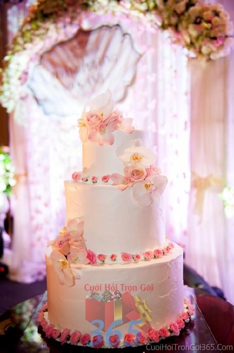 Trang trí bánh kem tông trắng hồng pastel với hoa tươi hồng, phong lan, cẩm chướng cho sân khấu tiệc nhà hàng ngày đám cướiTRBC27 : Mẫu cưới hỏi trọn gói 365 của công ty dịch vụ trang trí nhà tiệc cưới hỏi đẹp rẻ uy tín ở tại quận Tân Phú Sài Gòn TPHCM Gò Vấp