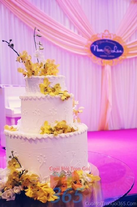 Trang trí bánh kem tông trắng vàng với hoa tươi phong lan trắng vàng cho sân khấu tiệc nhà hàng ngày đám cướiTRBC30 : Mẫu cưới hỏi trọn gói 365 của công ty dịch vụ trang trí nhà tiệc cưới hỏi đẹp rẻ uy tín ở tại quận Tân Phú Sài Gòn TPHCM Gò Vấp